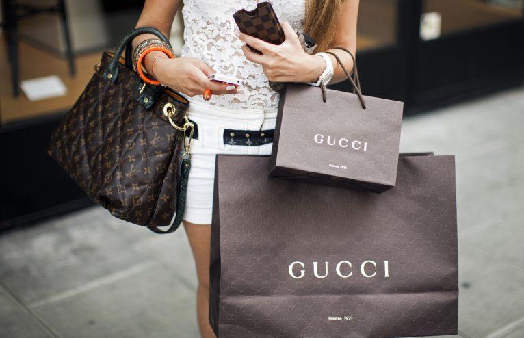 En la imagen se ve a una mujer con diversas bolsas en la mano.