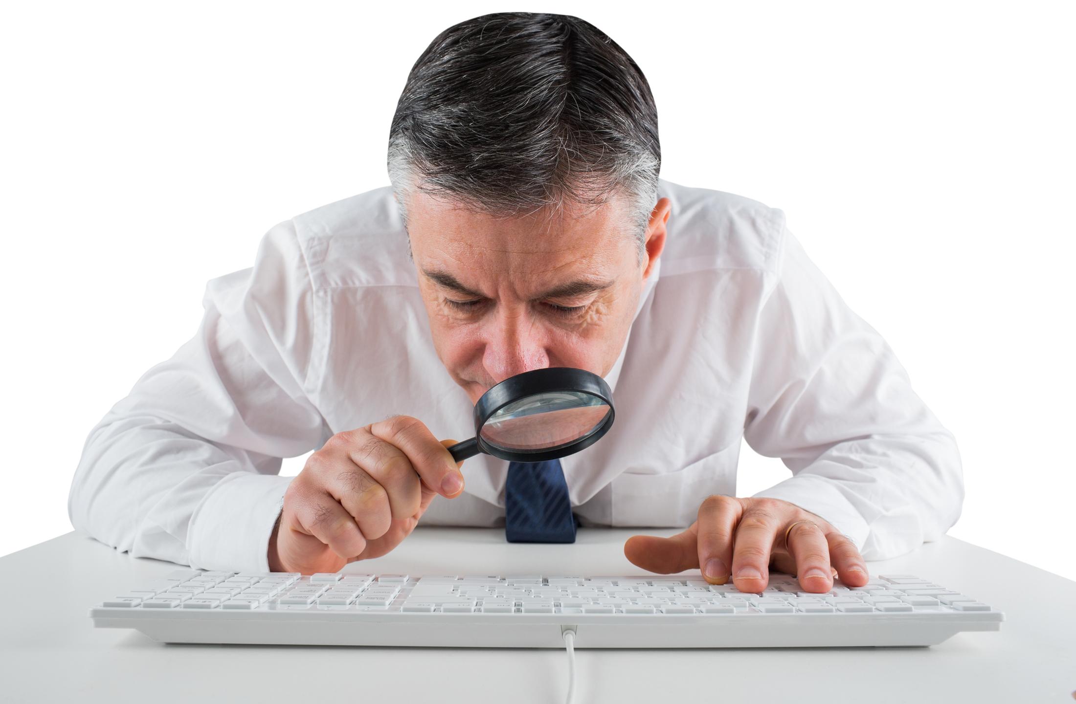 un hombre revisando con lupa el teclado