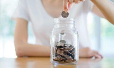 mujer depositando una moneda en un recipiente