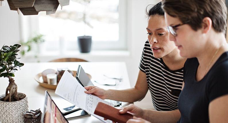 dos mujeres viendo unos documentos
