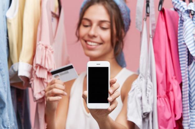 Mujer feliz con celular en la mano y tarjeta comprando ropa