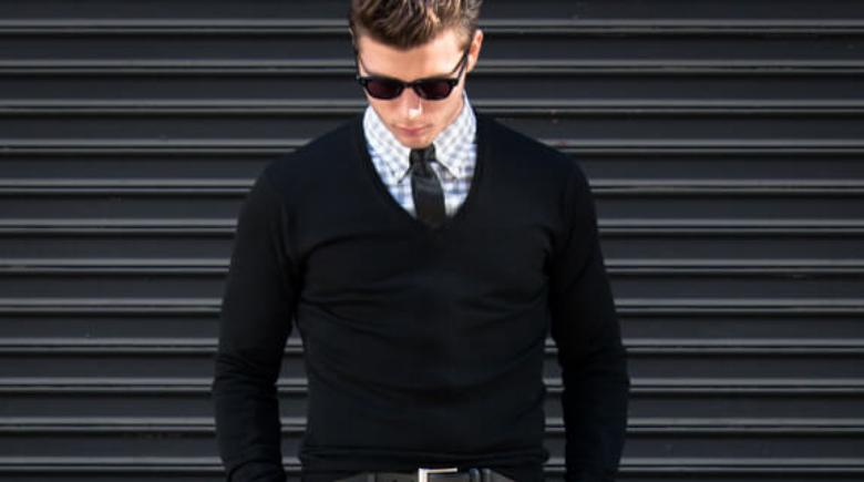 Hombre con camisa abotonada y suéter.
